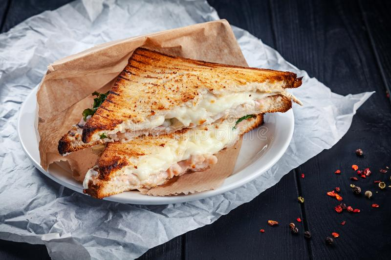 Close up on grilled sandwich with salmon and melted cheese and lettuce. Snack. Fast food for lunch. Sandwich served on white plate. On dark wooden background royalty free stock images