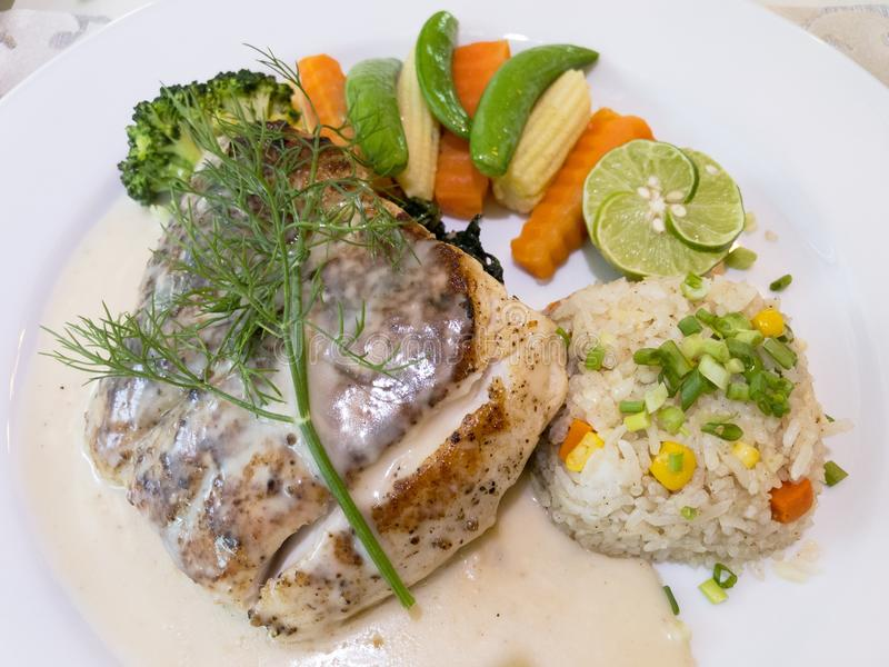Close-up grilled sea bass steak served with white wine sauce, fried rice with butter, and cooked vegetables on white plate. royalty free stock image