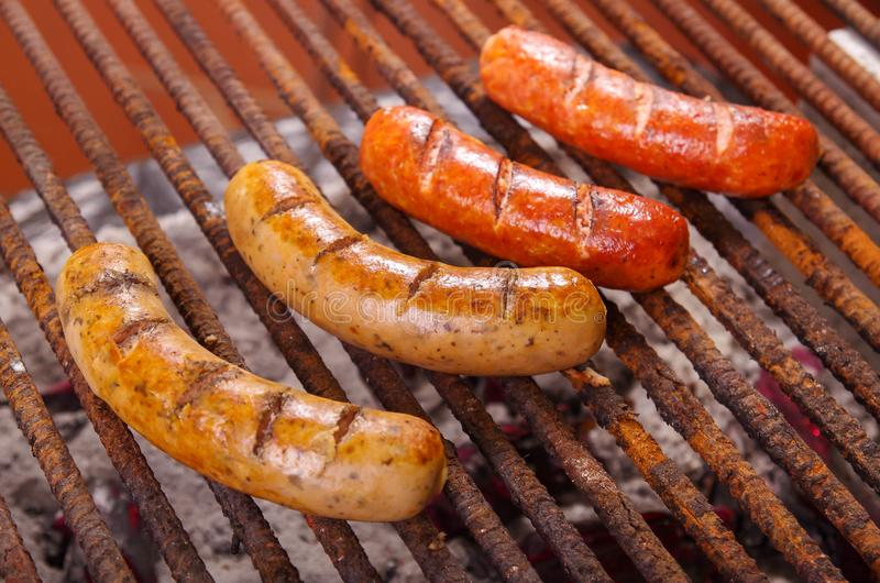 Close up of grilling sausages on barbecue grill. BBQ in the garden. Bavarian sausages royalty free stock image
