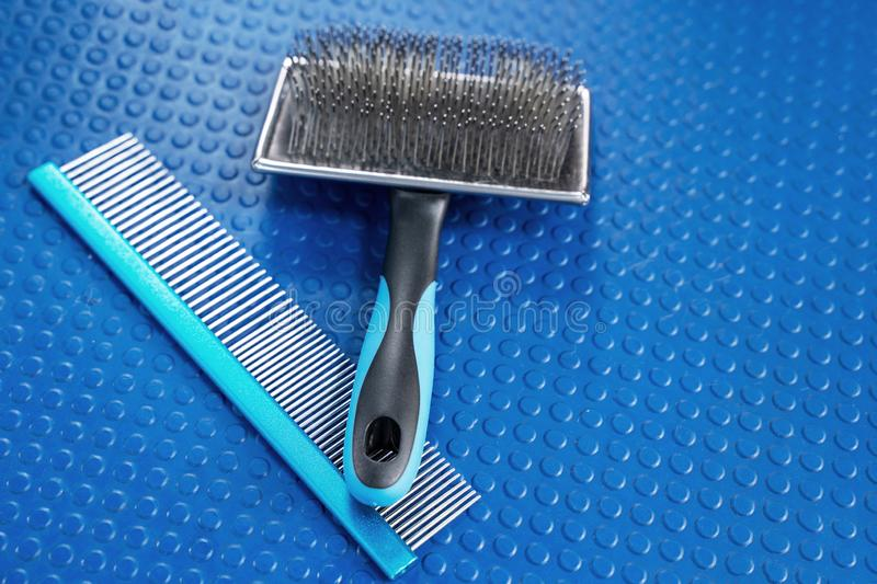 Close up grooming brush and special professional comb for dog and cat grooming. Bright blue rubber mat background. Concept of pets hair care and treatment stock photography