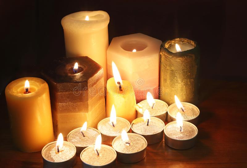 Group of burning candles in the dark stock photography