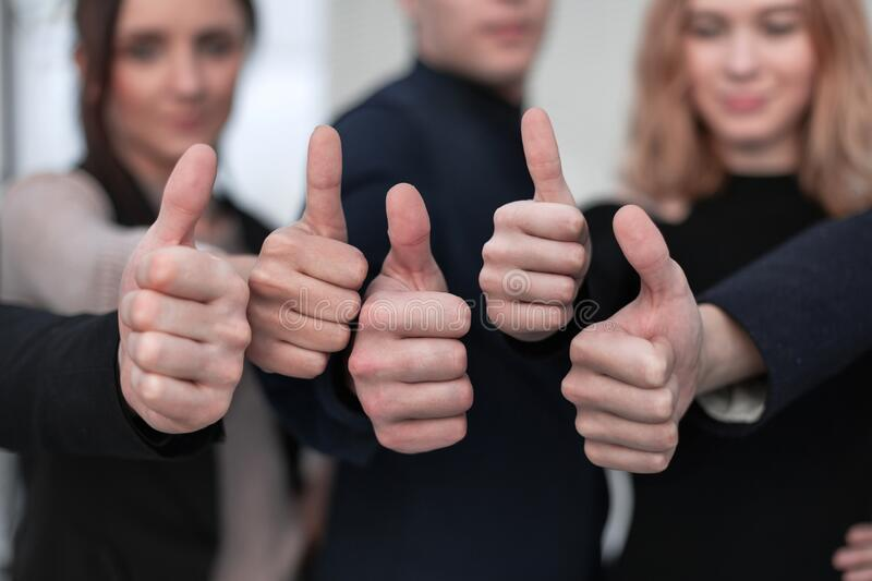 Close-up Of People`s Hand Showing Thumb Up Sign Against stock photos