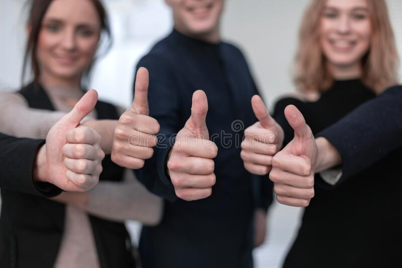 Close-up Of People`s Hand Showing Thumb Up Sign Against stock photo