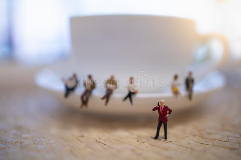 Close up of group of businessman miniature figure standing and make phone call with white cup of coffee stock image