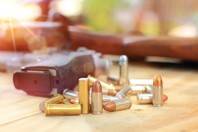 Close up group in flare light and pistol with bullet on table wooden for outdoor sport and hunting royalty free stock photos