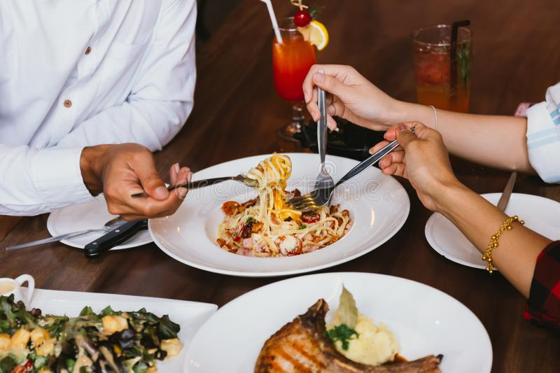 Close up of group of friends hands with a fork having fun eating and having italian dinner together. royalty free stock photography