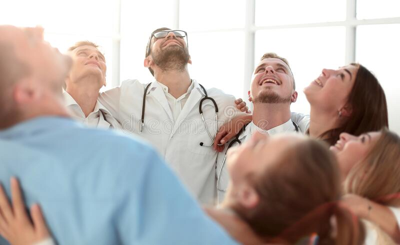 Close up. group of happy doctors standing in a circle stock photo