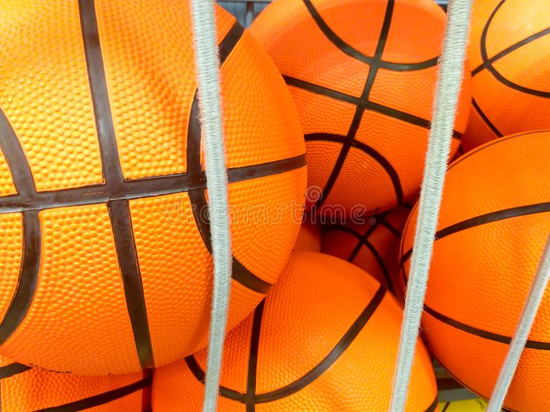 group of many new basketball orange balls with black lines at a sport shop ready to be sold behind some elastic white strings royalty free stock photo