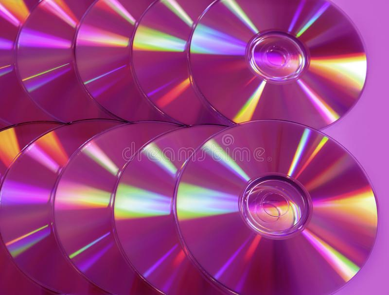 CD DVD disc colorful compact background rainbow shine pantone ultra violet pink purple 800080 lilac. Close up group of pink and purple DVD discs. Background from royalty free stock image
