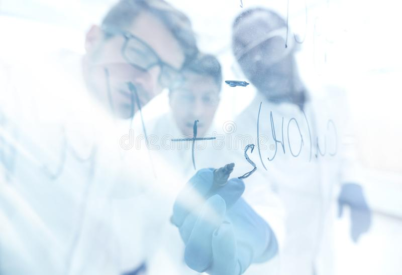 Close up.a group of scientists recording the formula on a glass stock images