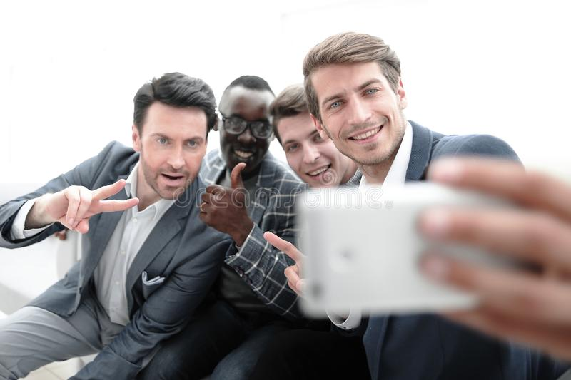 Close up.a group of young employees takes a selfie royalty free stock images
