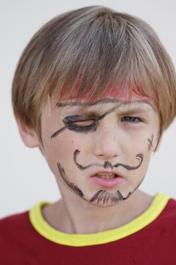 Close-up of grumpy pirate boy. A close-up portrait of a grumpy angry pirate boy royalty free stock image