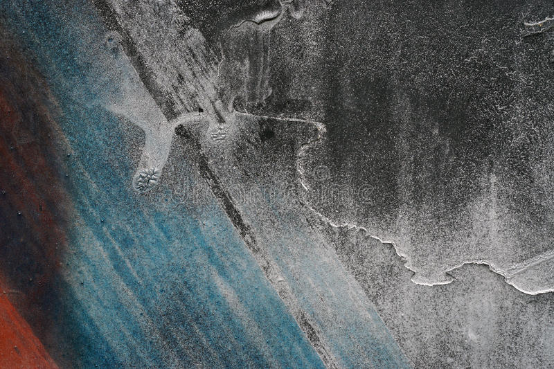 Close up of grungy rough scratched grey metal background. Close up of grungy rough scratched grey metal surface with red and blue details - Colorful abstract stock images