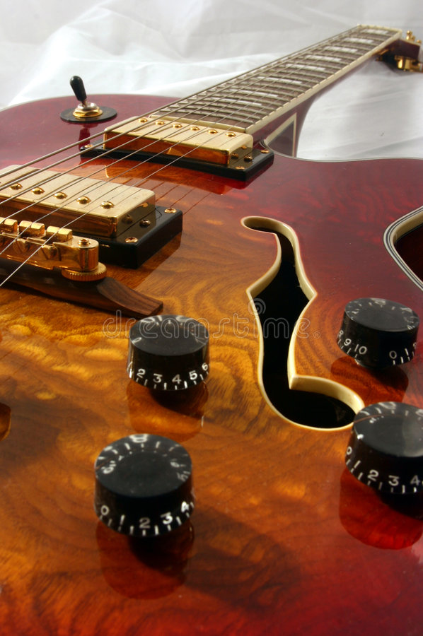 Close up guitar. Shot looking up a wooden semi accoustic guitar towards the neck showing pattern and colour of the wood, controls strings and piuck ups stock photo