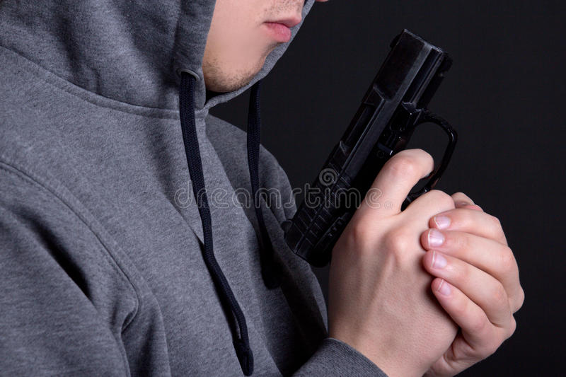 Close up of gun in male hands over grey royalty free stock photography