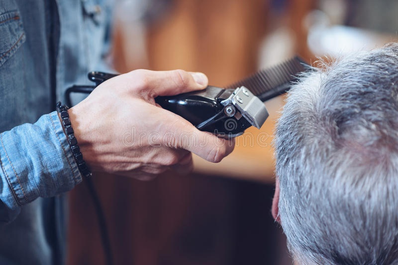 Close up of a hair cutting machine being in barbers hands. Professional equipment. Close up of hair cutting machine being I barbers hands while being used for stock photo