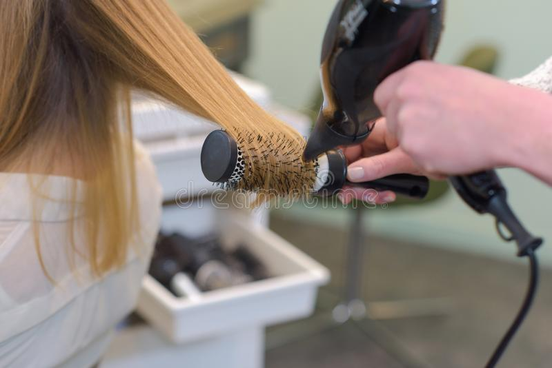 Close up hairdresser drying female clients hair stock photos