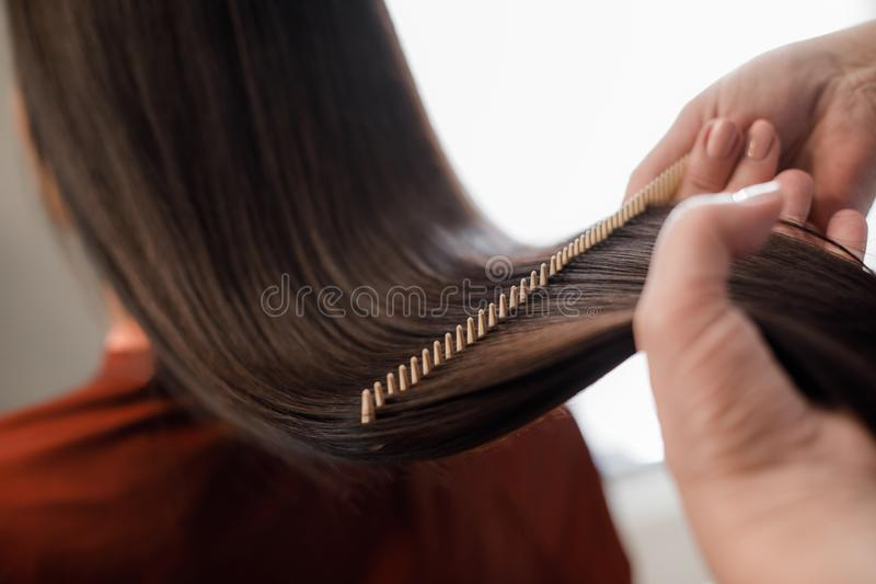 Hairdresser combing hair after styling in beauty salon royalty free stock photography