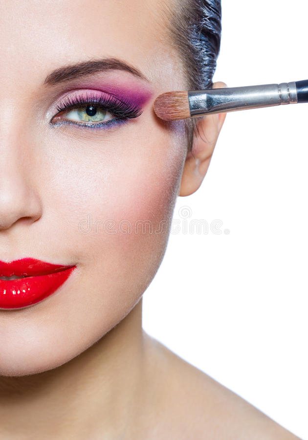 Close up of half-face of girl applying make-up stock photo
