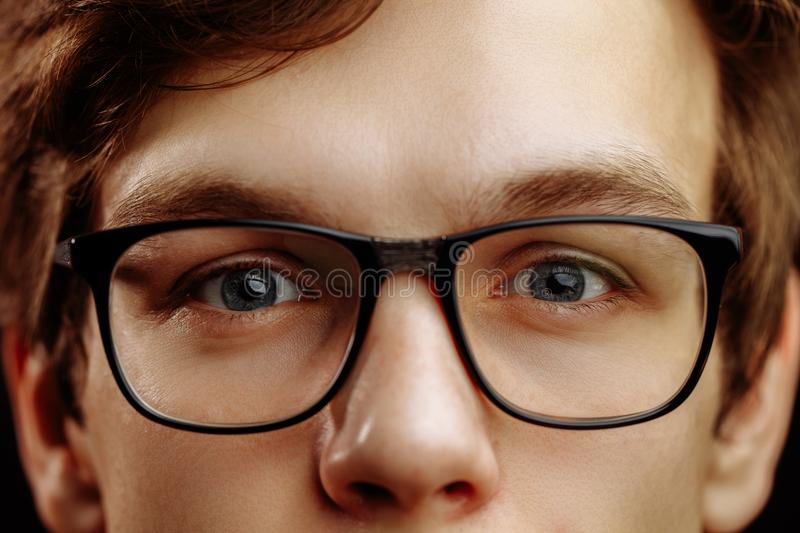 Close up half face of handsome fair-haired male with kind blue eyes stock photography