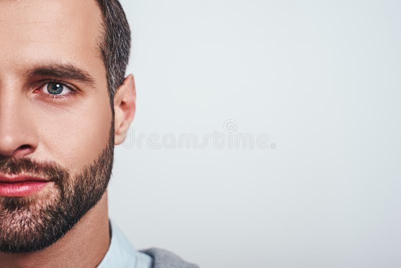 Close-up half face portrait of a smiling attractive man with a stubble looking at camera stock photos