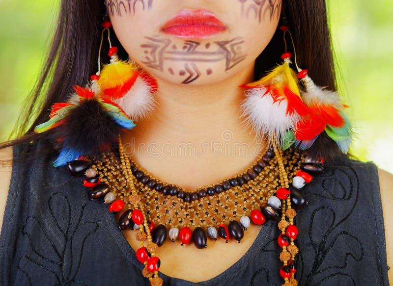 Close-up half gezicht die van mooie exotische vrouw uit de Amazone met gezichtsverf en zwarte kleding, ernstig voor camera stelle stock foto