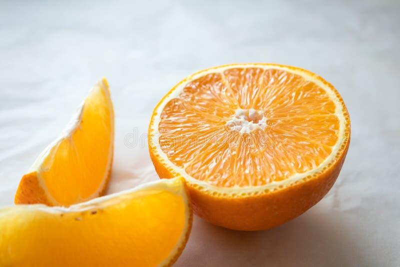 Close-up half of orange and slice on light table surface. Fresh citrus fruit, horizontal stock image