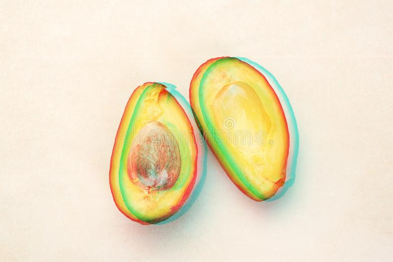 Close up of half sliced ripe avocado on white table with glitch effect royalty free stock photos