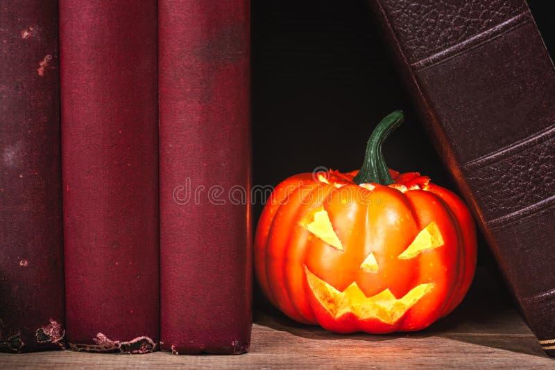 Halloween pumpkin between old books stock image