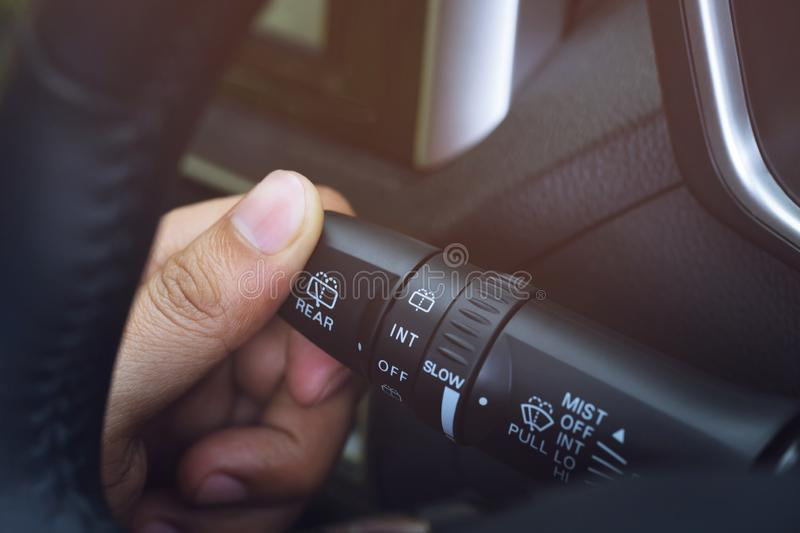 Close up hand adjusting rain windscreen wiper knob control stick switch speed of screen front car. stock image