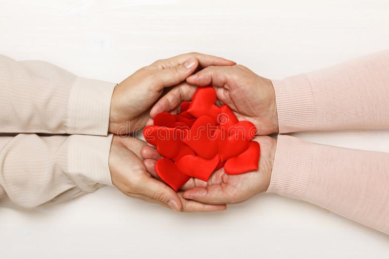 Close-up of the hand of an adult daughter and an older mother, holding together many hearts in their palms. Top view. royalty free stock photos
