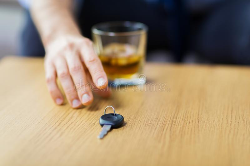 Close up of hand with alcohol and car key on table. Alcohol abuse, drunk driving and people concept - close up of male driver hand with whiskey glass taking car royalty free stock photo