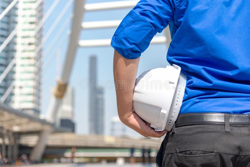 Close up hand architect worker holding white helmet a for workers security control at city site. Engineer inspector construction b royalty free stock photo