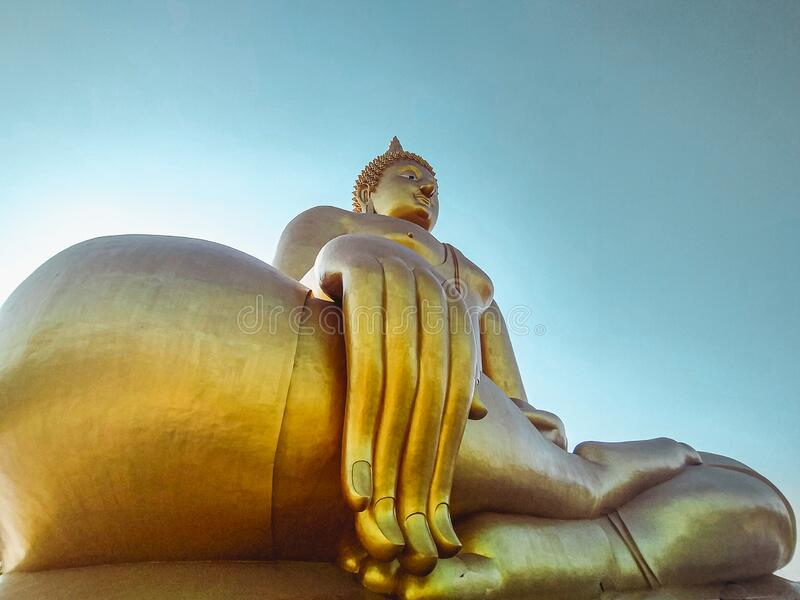 Close up hand of big Buddha statue with blue sky at Wat Tha Muang Thailand. The most specifically iconic Golden Buddha statues.  stock photos
