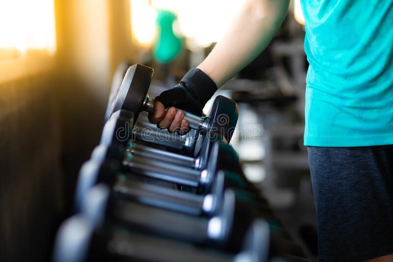Close up hand bodybuilder lifting dumbbell weights at fitness gym. Exercise is the Lifestyles of healthy royalty free stock photo