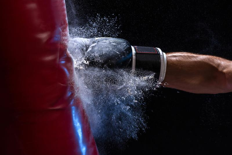 Close-up hand of boxer at the moment of impact on punching bag over black background stock images