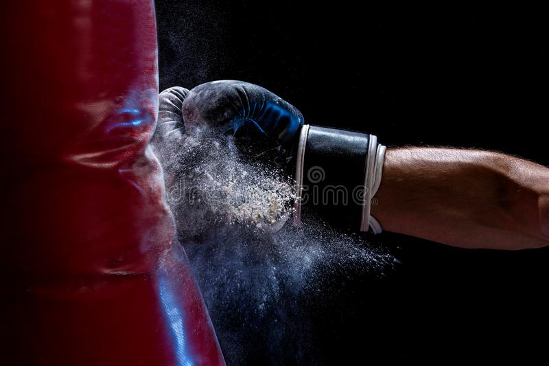 Close-up hand of boxer at the moment of impact on punching bag over black background. Strength and motivation. Studio shot stock photography