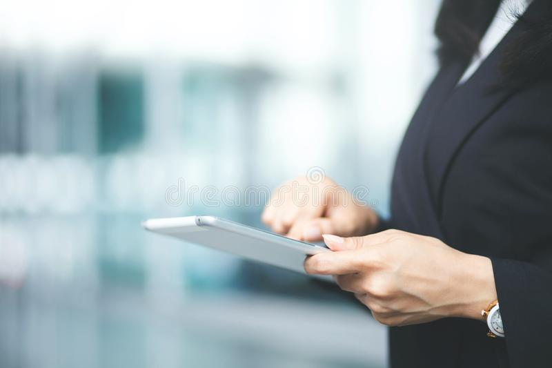 Close up hand business woman working using a digital tablet pc device while standing in front stock image