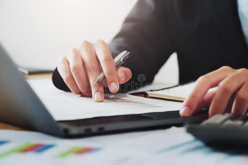 close-up hand of businessman analyzing investment chart on paperwork with laptop in office. concept finance and accounting royalty free stock photography