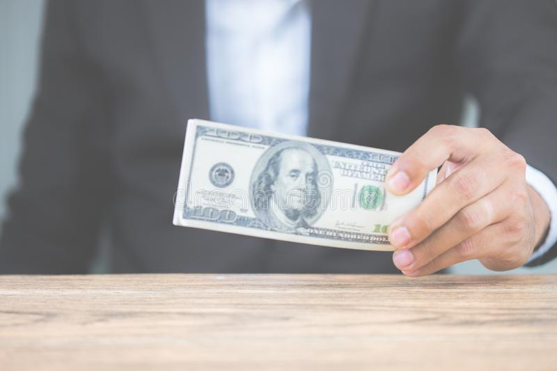 Close up hand of businessman holding money dollar bills on wooden table. Using as concept of corruption , Business corruption, royalty free stock image