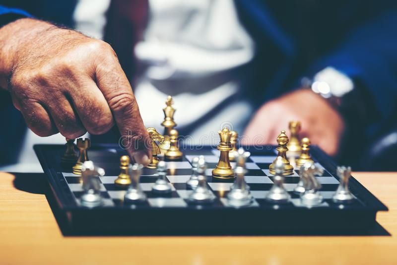 Close up hand of businessman moving chess figure in competition success play and thinking for management and planning work stock image