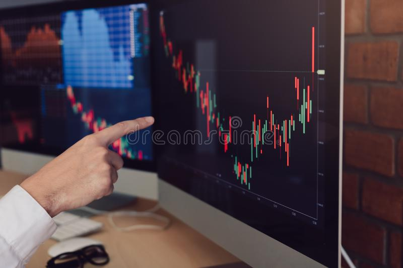 Close up of hand businessman pointing graph and analysis stock market on computer in office royalty free stock image