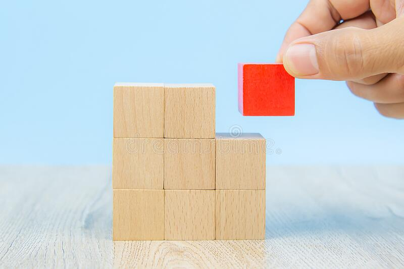 Close-up hand choose a cube shape wooden block toy stacked without graphics for Business design concept and activity for child fou. Ndation practice skills stock images