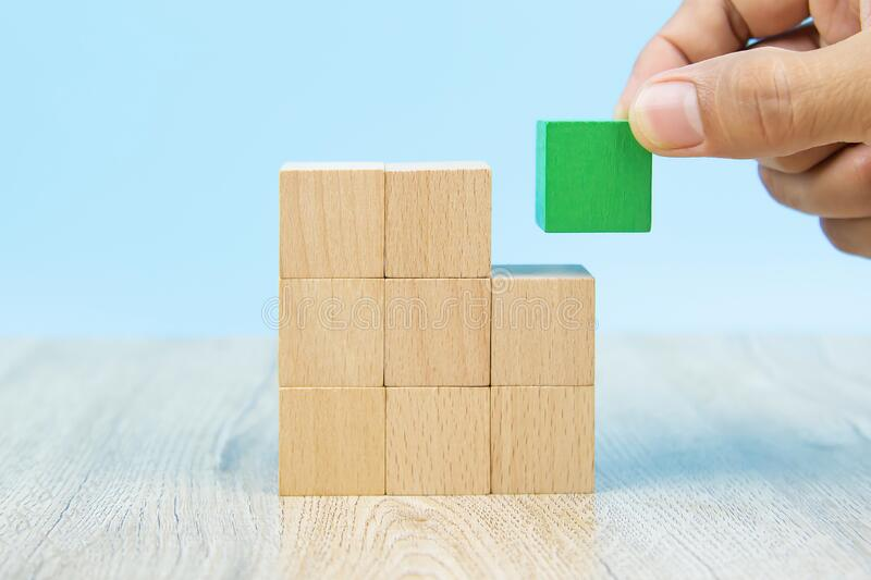 Close-up hand choose a cube shape wooden block toy stacked without graphics for Business design concept and activity for child fou. Ndation practice skills royalty free stock image
