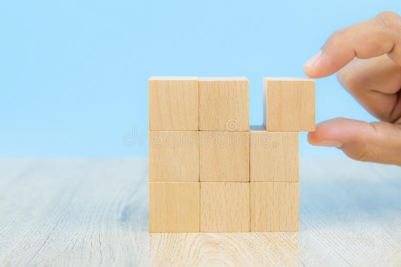 Close-up hand choose a cube shape wooden block toy stacked without graphics for Business design concept and activity for child fou. Ndation practice skills royalty free stock photography