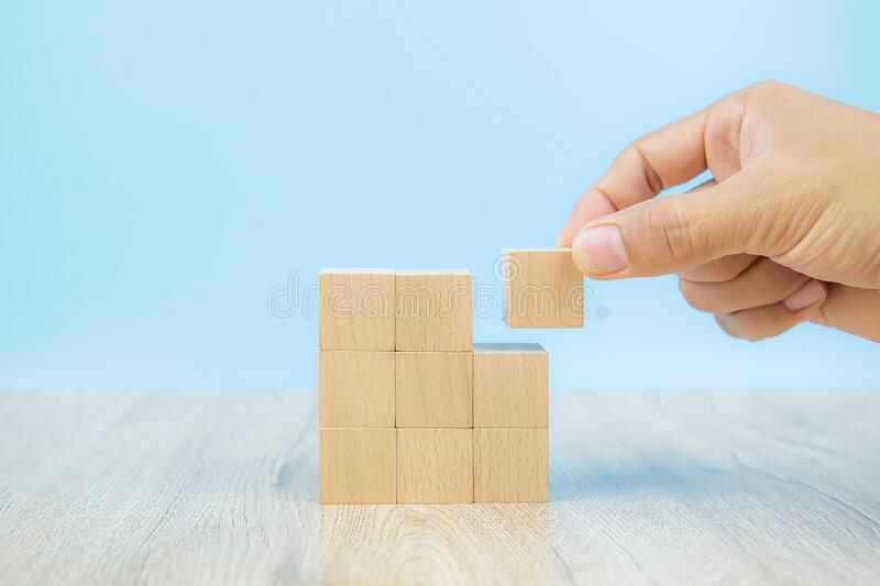 Close-up hand choose a green wooden block toy stacked in square shape without graphics for Business design concept and activity. For child foundation practice stock photography