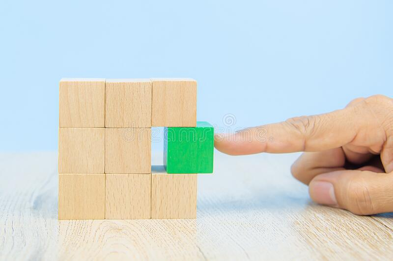 Wooden block toy stacked in square shape without graphics for Business design concept and activity. Close-up hand choose a green wooden block toy stacked in stock photography