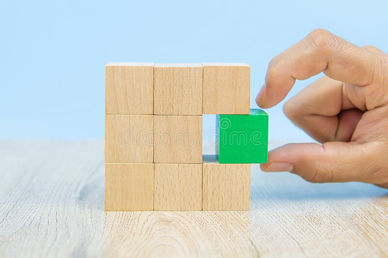 Close-up hand choose a green wooden block toy stacked in square shape without graphics for Business design concept and activity. For child foundation practice royalty free stock photography