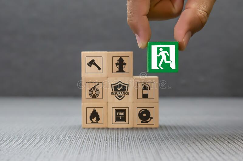 Close-up hand choose a wooden toy blocks with fire exit icon for fire safety protection. Concepts stock image