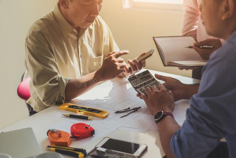 Close up hand of civil engineer or architect business using calculator about calculate the cost with for working building plan royalty free stock photo